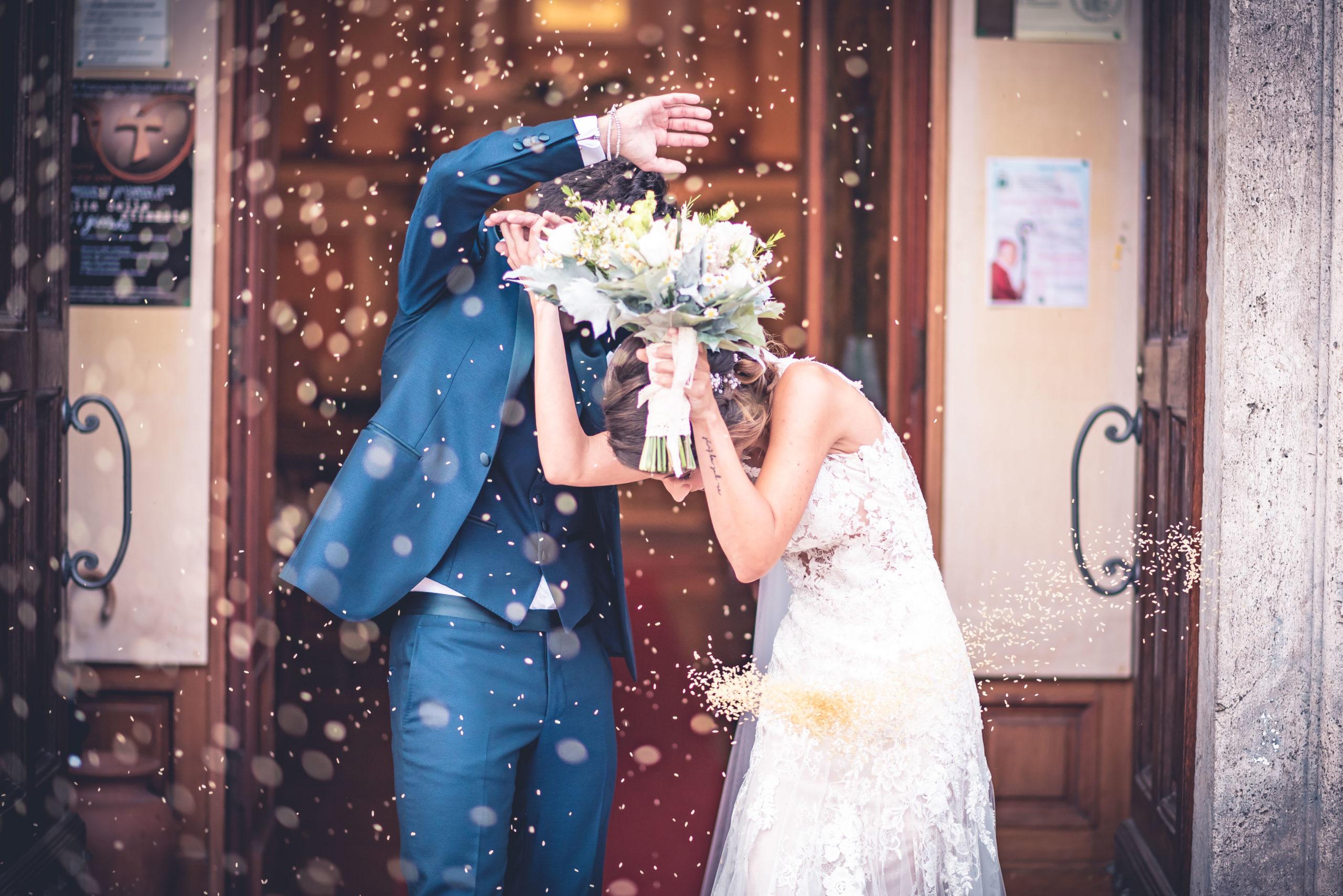 portfolio sposi si riparano dal lancio del riso