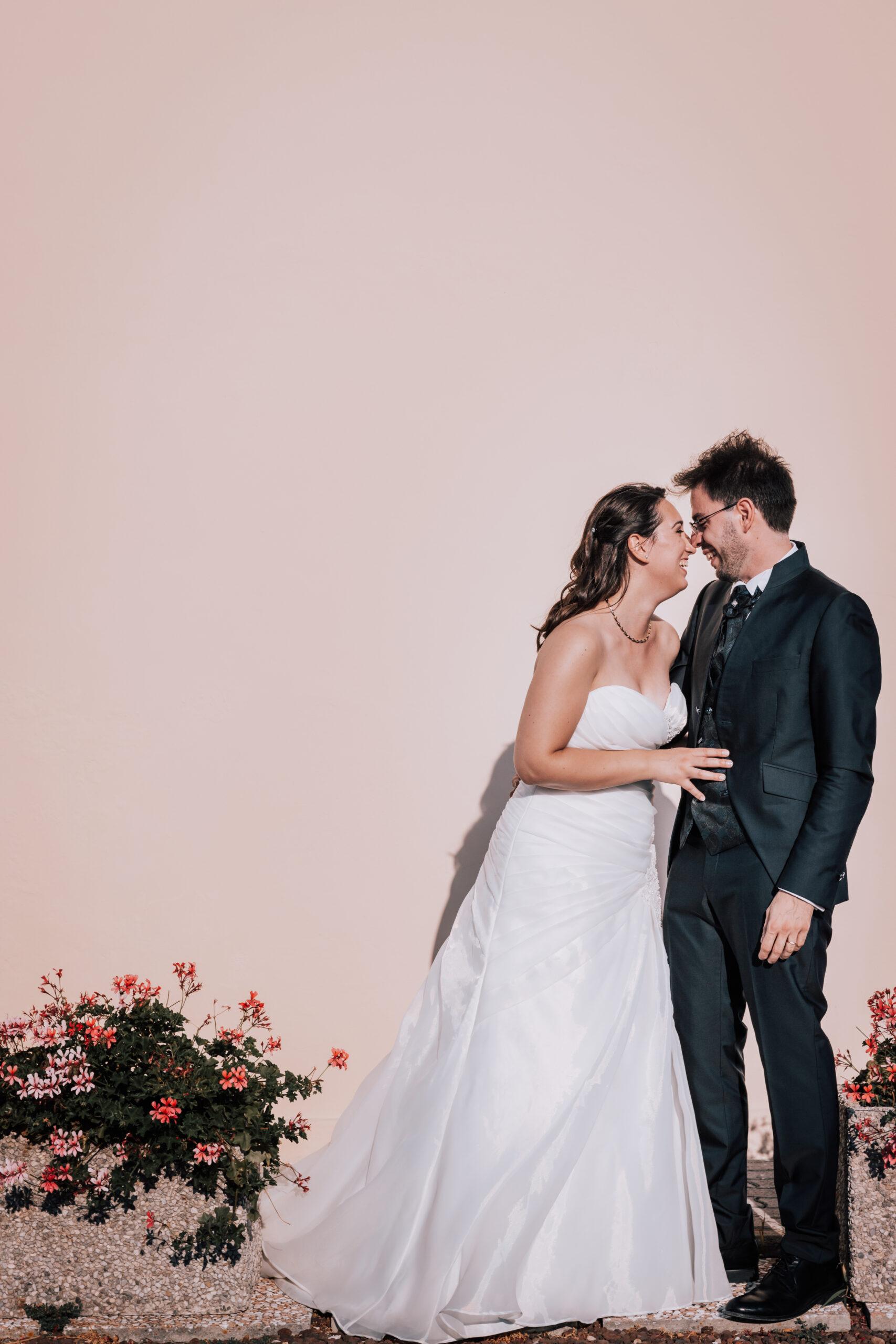 sposi su sfondo rosa pastello
